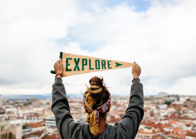 """Person Stands Holding An """"explore"""" Flag Overlooking The City Skyline Of Madrid, Spain"""